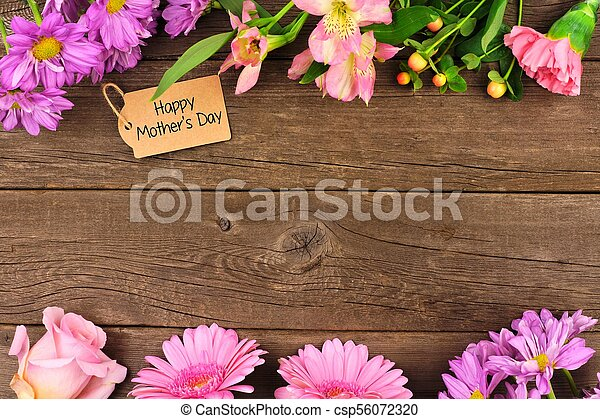 Double border of flowers with Mothers Day gift and tag against rustic wood - csp56072320