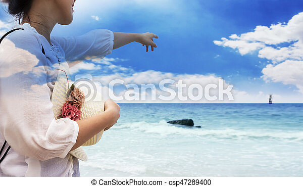 Double exposure of smiling young woman pointing finger blue sky on the beach - csp47289400