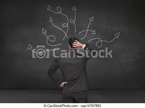 Doubtful businessman looking at arrows - csp14767883