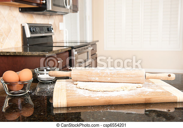 Dough and rolling pin in kitchen - csp6554201