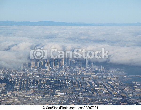 Downtown San Francisco aerial view taken from an airplane as fog begins to cover the city with buildings, highways, and wharf in California. - csp20207301