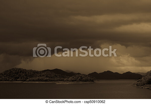 Dramatic dark storm clouds before rainy over Lake in Thailand