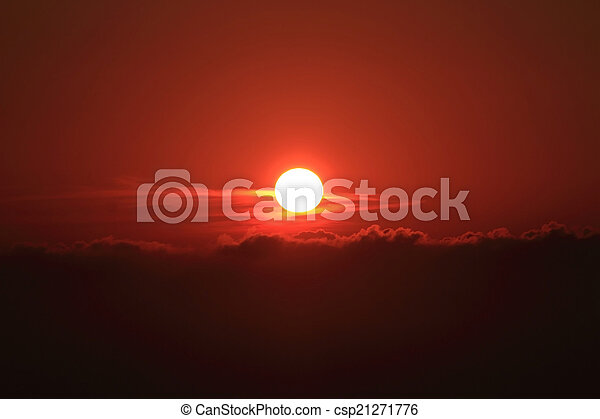 Dramatic red sunset with center sun and dark clouds - csp21271776