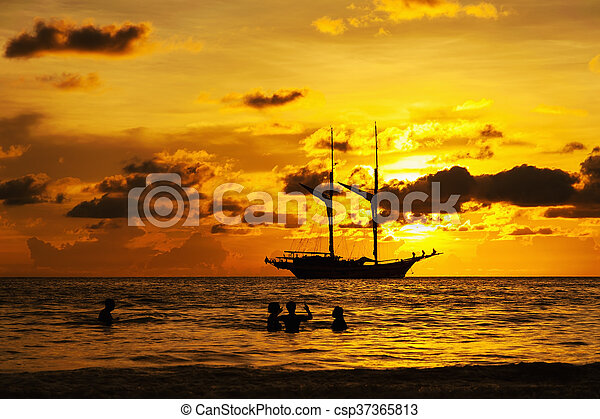 Dramatic sea and transport boat in color of sunset - csp37365813