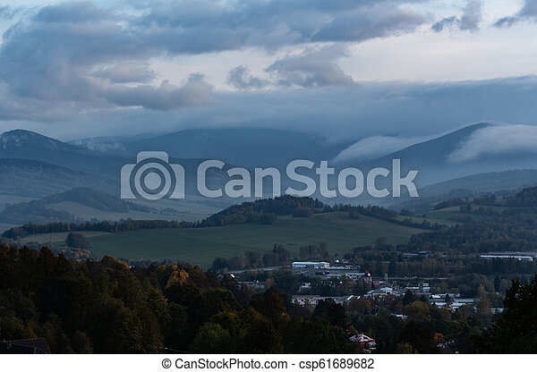 Dramatic view in the mountains before the storm - heavy gray clouds float over green mountain ridges - csp61689682