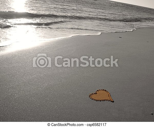 Drawing a heart in the sand - csp6582117