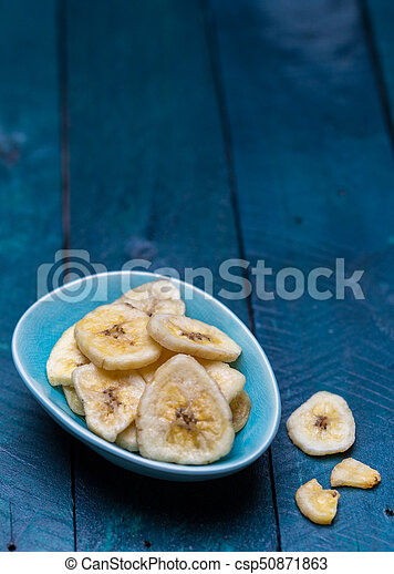 Dried banana in a bowl on petrol colored wooden background - csp50871863