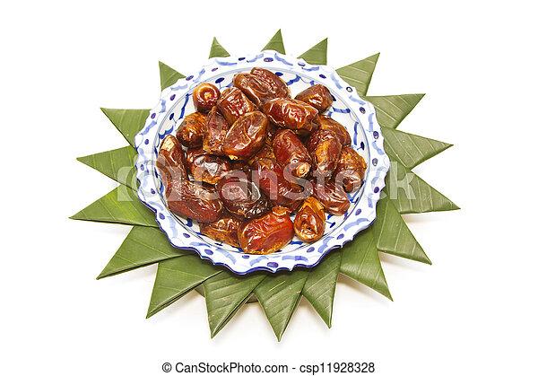 dried dates in ceramic bowl on banana leaf - csp11928328