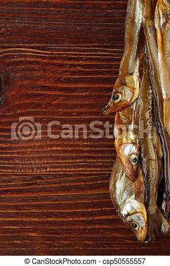 Dried fish with salt on wooden background - csp50555557