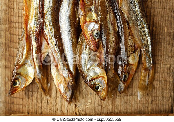 Dried fish with salt on wooden background - csp50555559