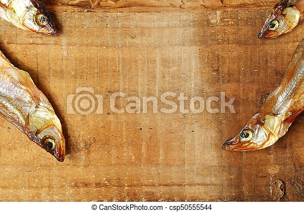 Dried fish with salt on wooden background - csp50555544