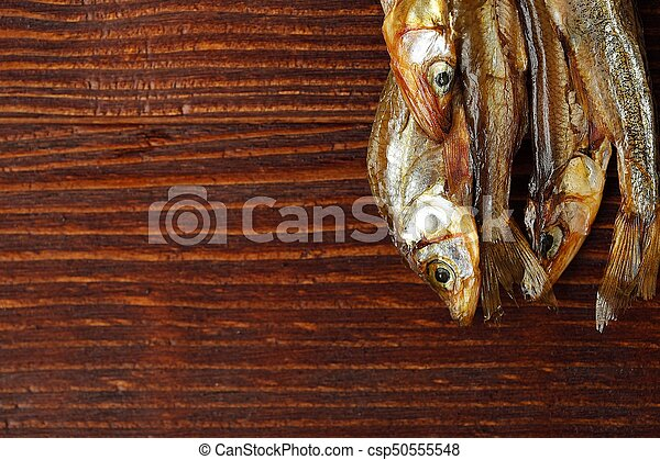 Dried fish with salt on wooden background - csp50555548