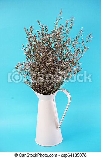 dried flower bouquet in metal vase with blue background - csp64135078