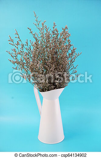 dried flower bouquet in metal vase with blue background - csp64134902