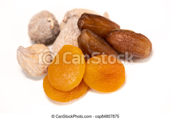 Dried fruit composition, figs, apricots, dates, on white background - csp84807875