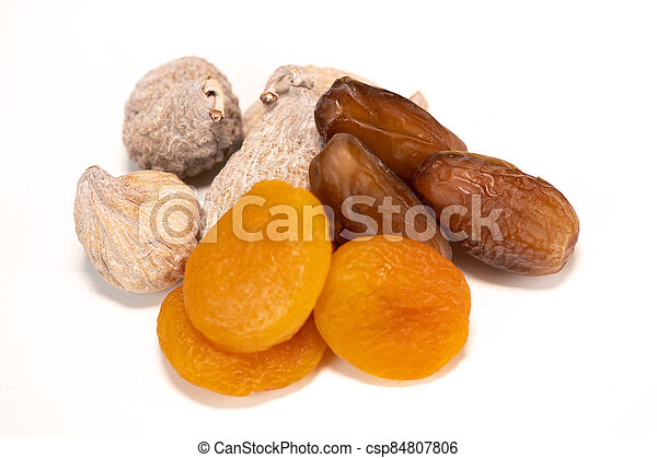 Dried fruit composition, figs, apricots, dates, on white background - csp84807806