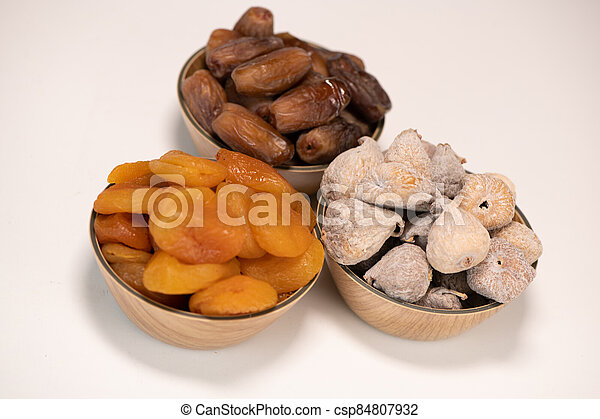 Dried fruit composition, figs, apricots, dates, on white background - csp84807932