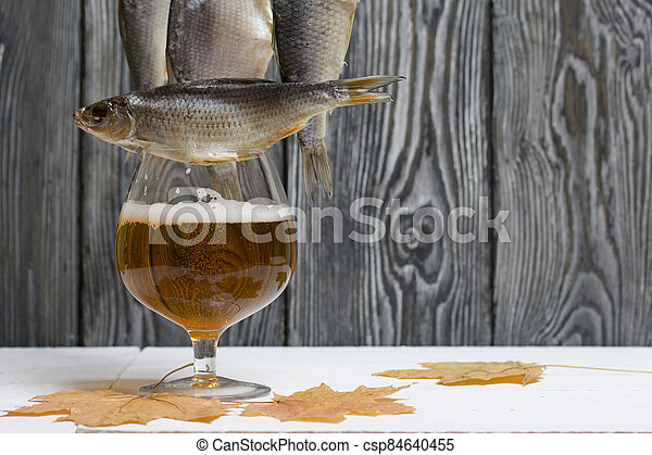 Dried river fish hangs on a rope. Nearby is a glass of beer and dried maple leaves. There is a roach on the glass. - csp84640455