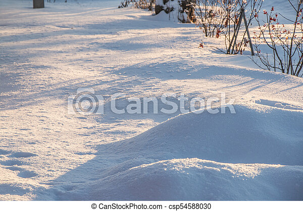 drifts of pure snow in the rays of the evening sun at sunset - csp54588030