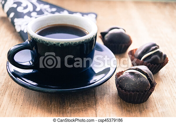 drink cup of coffee with chocolate candies - csp45379186