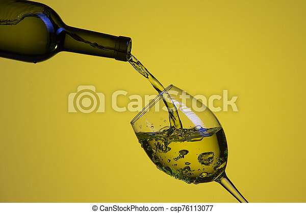 Drink Pouring Out of The Bottle On The Left Hand Side to Whineglass with Colorful Liquid and Droplets. Isolated Over Yello Background. - csp76113077