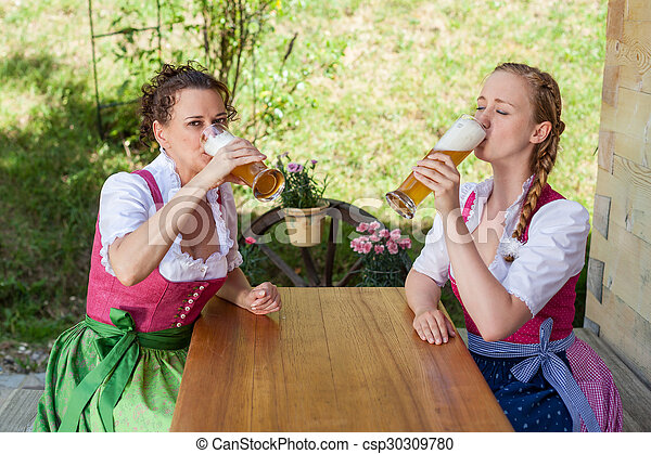 Drink Two women in Bavarian Dirndl with a beer - csp30309780