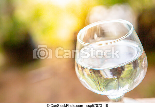 Drink water in glass over sunlight natural yello background - csp57073118