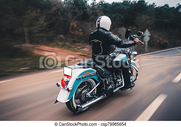 Driving blue motorcycle on the forest road - csp79985654