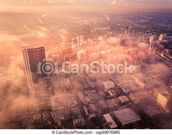 Drone aerial view of a misty foggy morning in a bustling downtown central business district - csp59076985