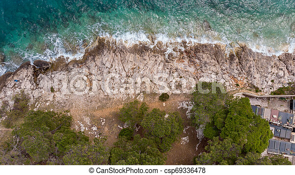 Drop down view of waves crashing into rocky shore. - csp69336478