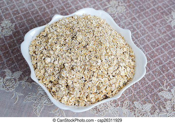 Dry oatmeal in a plate on table - csp26311929