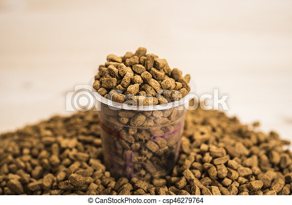 Dry pet nutrition with a measuring cup close up - csp46279764