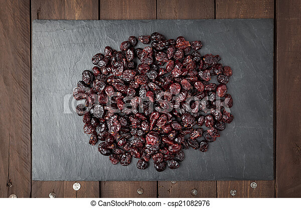 Dry red cranberries on a slate plate - csp21082976