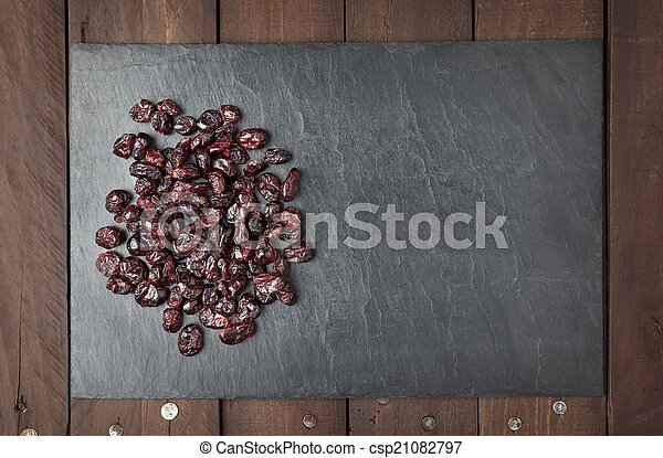 Dry red cranberries on a slate plate with copy space - csp21082797