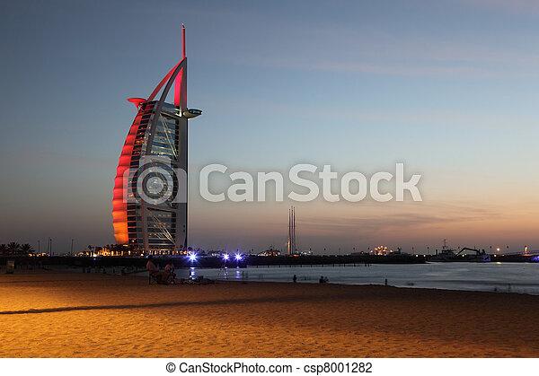DUBAI - APRIL 17: Burj Al Arab skyscraper near evening beach with sand and people in motion, 17 april 2010 in Dubai, UAE - csp8001282