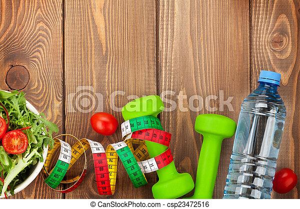 Dumbells, cinta métrica y comida saludable. Fitness y salud - csp23472516