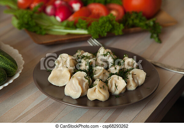 dumplings with herbs on a plate of vegetables - csp68293262