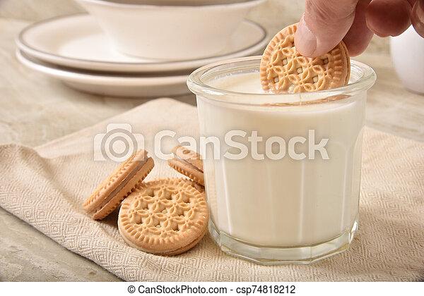 Dunking a cookie in milk - csp74818212
