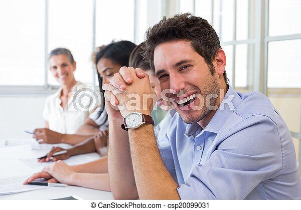 Un hombre de negocios casual riéndose durante la reunión - csp20099031