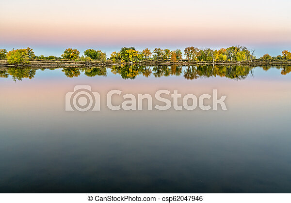 dusk over a calm lake with fall colors - csp62047946