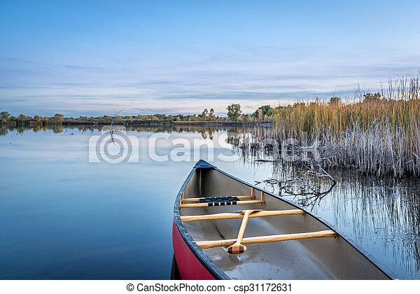 dusk over calm lake with a canoe - csp31172631