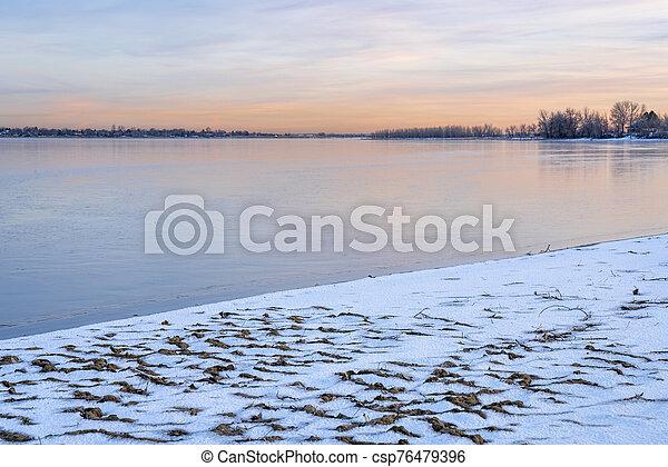 dusk over frozen lake in northern Colorado - csp76479396