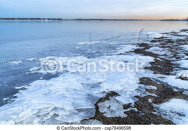 dusk over frozen lake in northern Colorado - csp76496598