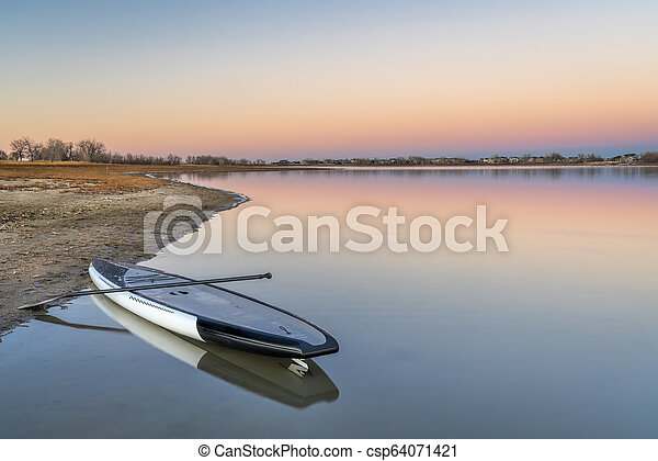 dusk over lake with a paddleboard - csp64071421