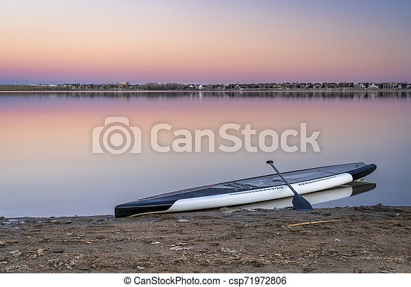 dusk over lake with a paddleboard - csp71972806