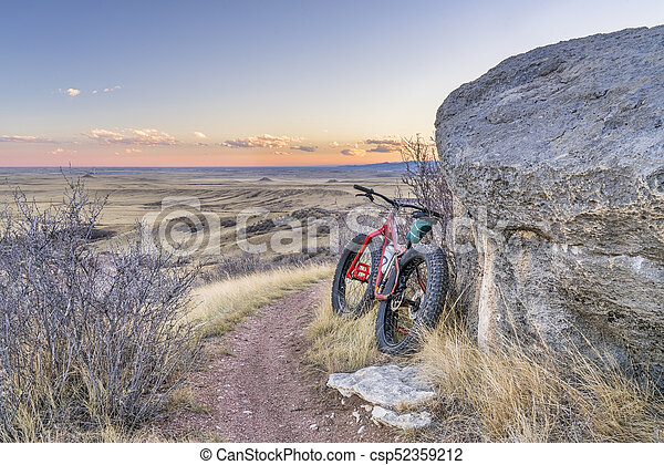 Dusk over prairie with fat bike - csp52359212