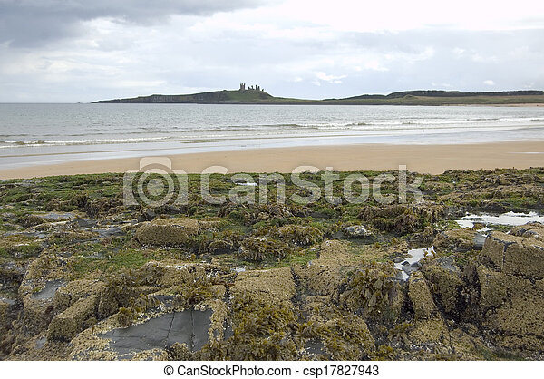 Dustanburgh with rocks and beach - csp17827943