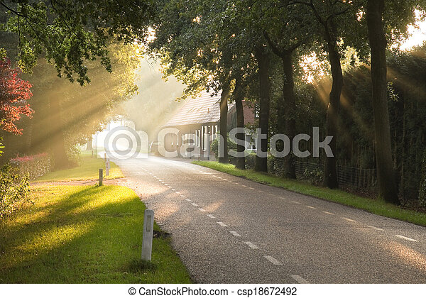 Dutch country road and farm with sun beams - csp18672492