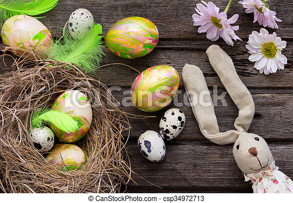 Easter background with colored eggs in nest and home made decoration on rustic wooden board - csp34972713