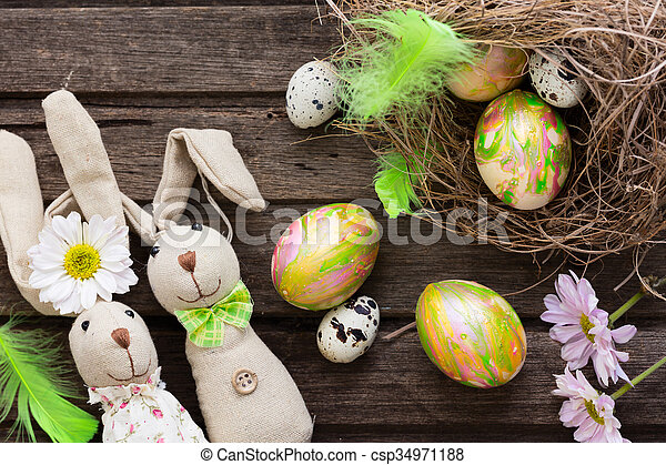 Easter background with colorful eggs in nest and home made bannies on rustic wooden board - csp34971188